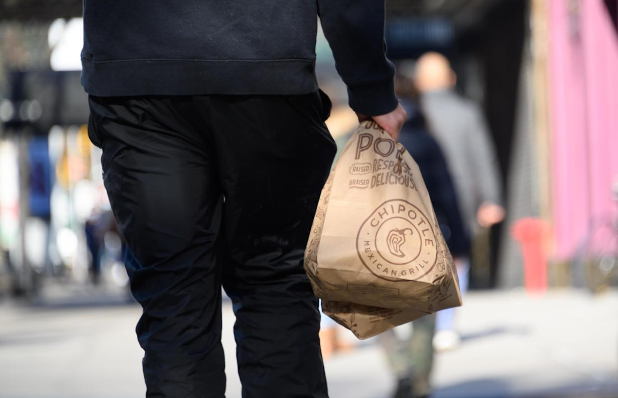 NEW YORK, NEW YORK - DECEMBER 11: A person carries a take out bag outside Chipotle on the Upper West Side on December 11, 2020 in New York City. Governor Andrew Cuomo announced that indoor dining would close on Monday December 14th due to an ongoing spike in COIVD-19 cases. (Photo by Noam Galai/Getty Images)