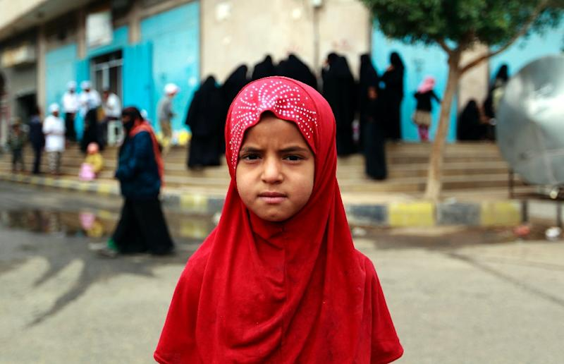 A Yemeni girl looks on as volunteers distribute food to poor families as part of an initiative organised by a local charity in the capital Sanaa, on February 24, 2016