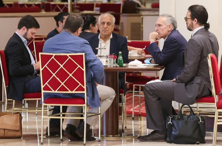 US special representative Zalmay Khalilzad (C) sits in a coffee shop ahead of a session of the peace talks between the Afghan government and the Taliban in the Qatari capital Doha