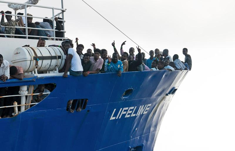 Rescued: migrants wave from aboard ship operated by the German NGO Mission Lifeline: AP