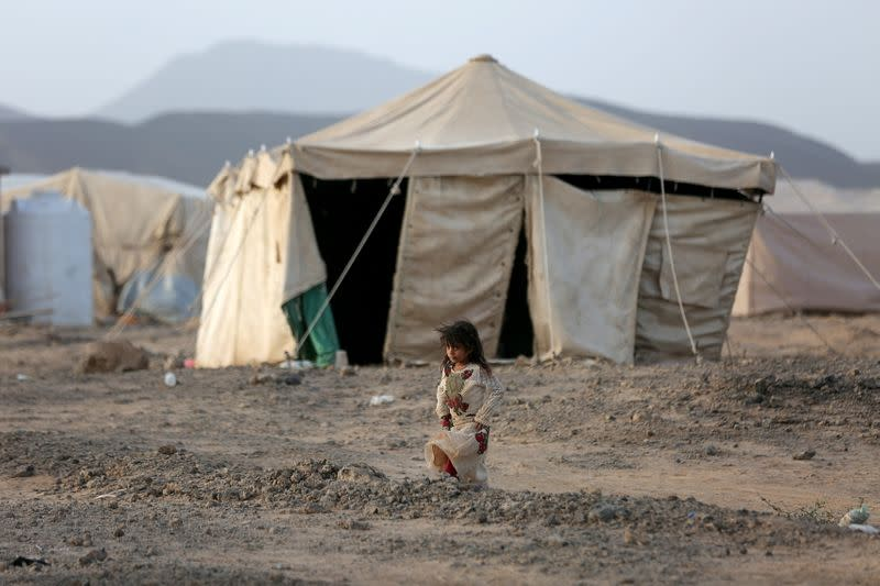 FILE PHOTO: Girl walks past a tent at a camp for internally displaced people (IDPs) in Marib