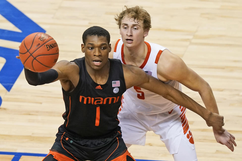 Miami forward Anthony Walker (1) looks for help as Clemson forward Hunter Tyson (5) defends during the second half of an NCAA college basketball game in the second round of the Atlantic Coast Conference tournament in Greensboro, N.C., Wednesday, March 10, 2021. (AP Photo/Gerry Broome)