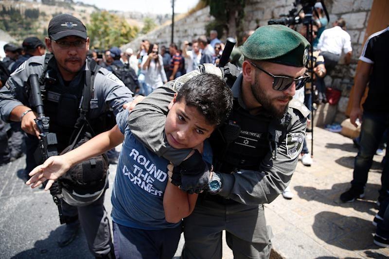 Israeli border guards detain a Palestinian youth outside the Lions Gate entrance to the Al-Aqsa mosque compound in Jerusalem's Old City on July 17, 2017 (AFP Photo/AHMAD GHARABLI)