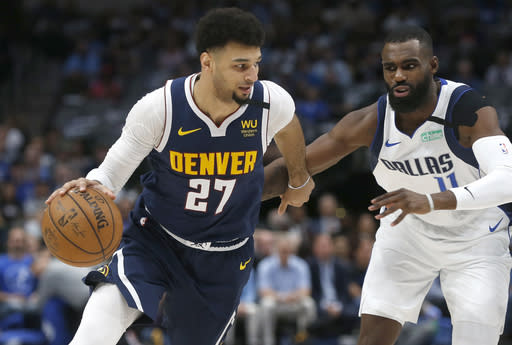 Denver Nuggets guard Jamal Murray (27) handles the ball as Dallas Mavericks guard Tim Hardaway Jr. (11) defends during the first half of an NBA basketball game Wednesday, March 11, 2020, in Dallas. (AP Photo/Ron Jenkins)