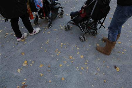 Filipino nannies stroll with children during their duty hours at a park in Tokyo November 29, 2013.REUTERS/Issei Kato