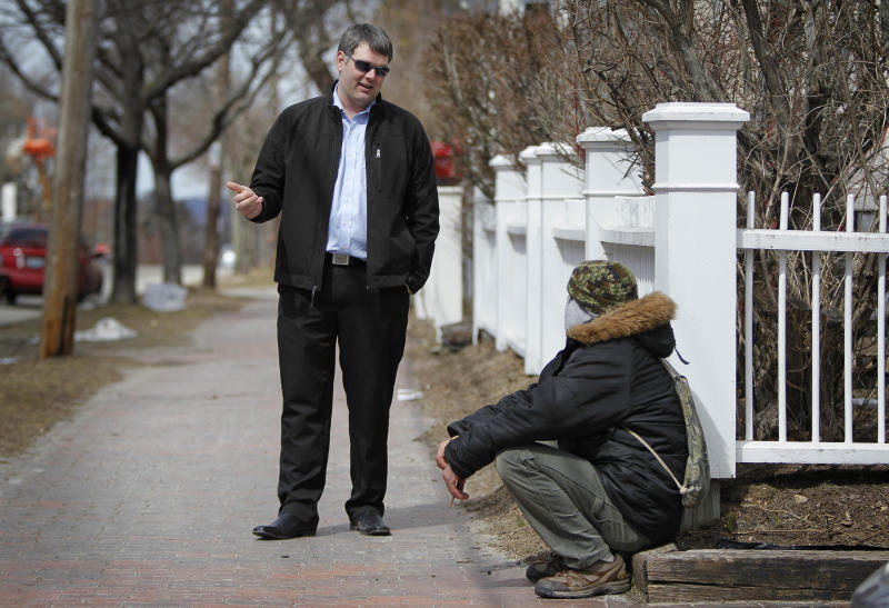 In this March 24, 2013 photo, former Marine Corps Cpl. Marshall Archer, left, a veterans' liaison for the city of Portland, Maine, speaks to a man on a street in Portland. Veterans groups are rallying to fight any proposal to change disability payments as the federal government attempts to address its long-term debt problem. They say they've sacrificed already. (AP Photo/Robert F. Bukaty)