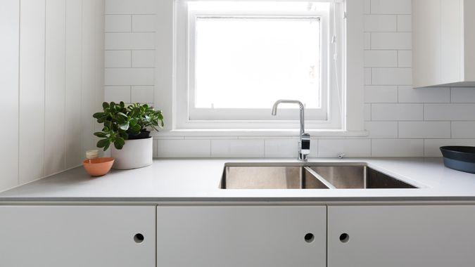 Close up details of contemporary white apartment kitchen with subway tiles.