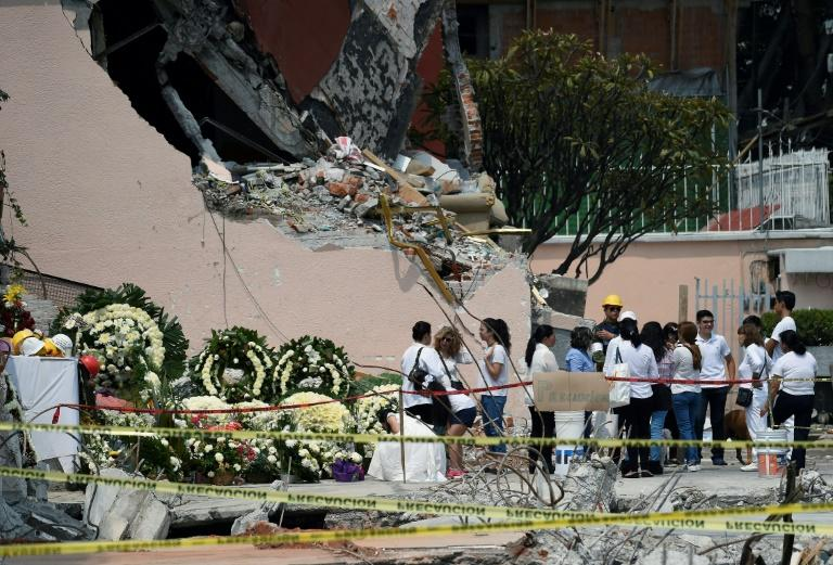 Wreaths are placed to honor the dead on the site where a building was flattened by the 7.1-magnitude quake in Mexico City on September 26, 2017