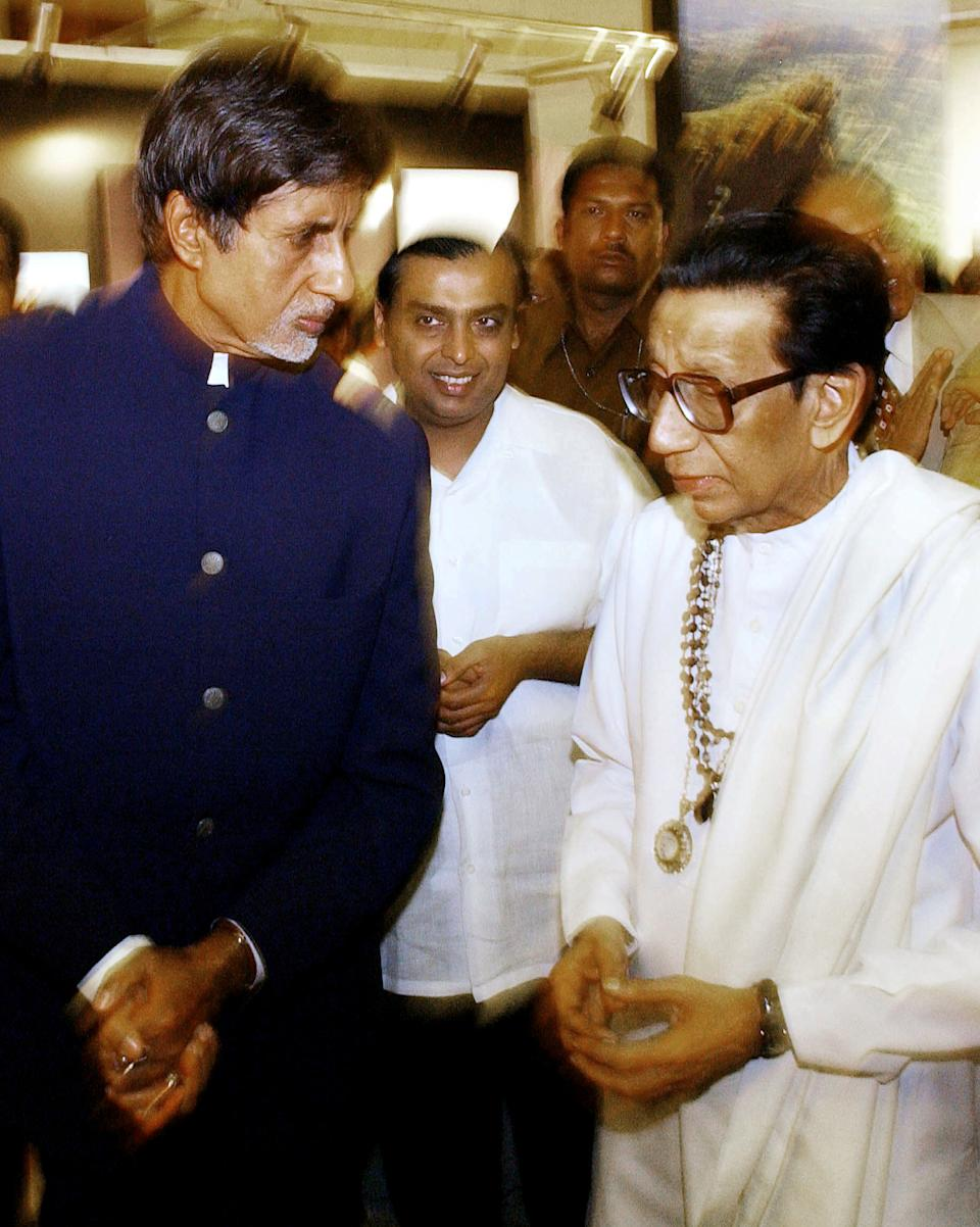 India's Shiv Sena party Chief Bal Thackeray (R) speaks to actor Amithab Bachchan (L) while Chairman of Reliance Industry Mukesh Ambani (C) looks on at the inauguration of Thakeray's son Udhav's aerial photographic exibition on the 'Forts of Maharashtra' at the Jahangir Art gallery in Bombay, 19 January 2004. Udhav has a collection of 4000 aerial pictures of 28 forts of the Indian state of Maharashtra of which few have been showcased.