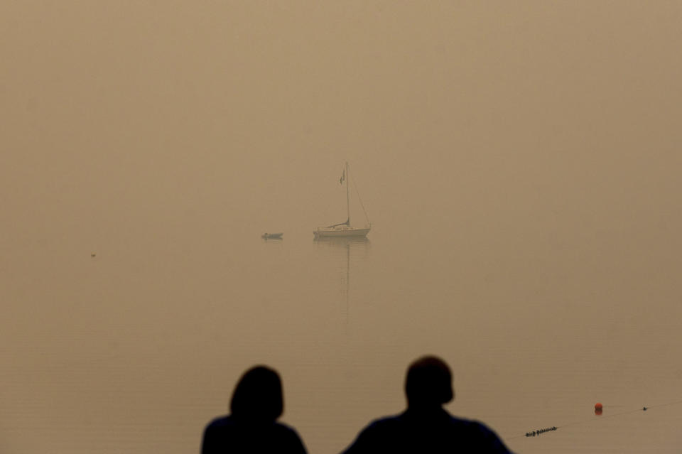 FILE - In this Friday, Aug. 27, 2021, file photo, a couple looks out on Lake Tahoe, which is blanketed by smoke from the Caldor Fire, in South Lake Tahoe, Calif. tate fire officials say evacuation orders for the area were reduced to warnings as of 3 p.m. Sunday, Sept. 5. Some 22,000 people had been forced to flee the popular resort and nearby areas last week as the Caldor Fire roared toward it. (AP Photo/Noah Berger, File)
