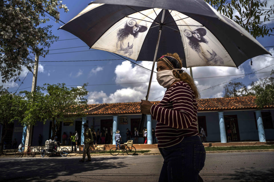 A woman wearing a mask amid the COVID-19 pandemic shades herself under the strong midday sun in Viñales, Cuba, March 1, 2021. Some Cubans are living on hope that new U.S. President Joe Biden will reverse at least some of the restrictions implemented by his predecessor. (AP Photo/Ramon Espinosa)