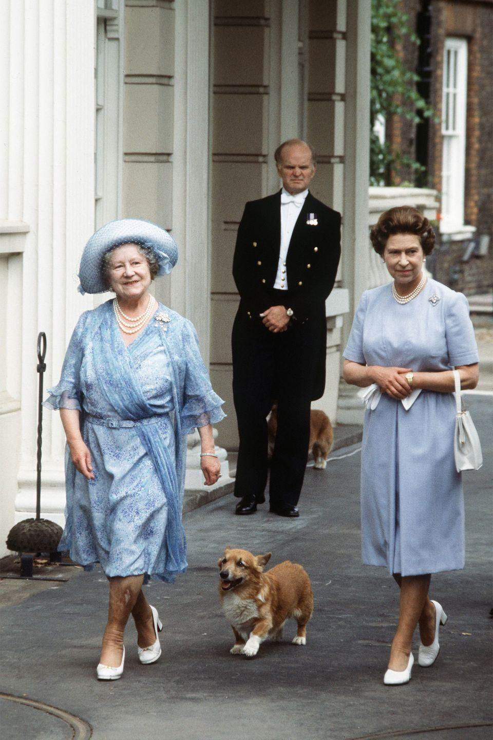 <p>The Queen Mother celebrated her 83rd birthday with her daughter Queen Elizabeth outside of Clarence House with her adorable corgi. The mother-daughter duo looked in-sync with their similar blue dresses and white heels.</p>