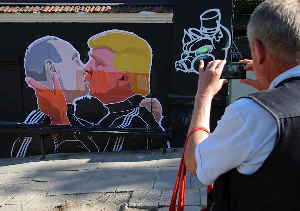 A man photographs a mural on a restaurant wall depicting US Presidential hopeful Donald Trump and Russian President Vladimir Putin greeting each other with a kiss in the Lithuanian capital Vilnius on May 13, 2016.