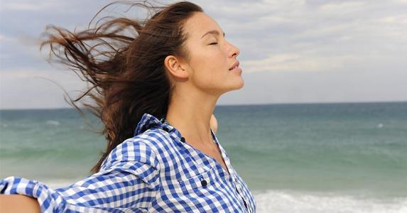 Woman standing in the wind by the shore | mangostock/Getty Images