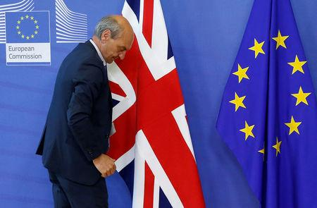 FILE PHOTO: A worker arranges flags at the EU headquarters as Britain and EU launch Brexit talks in Brussels