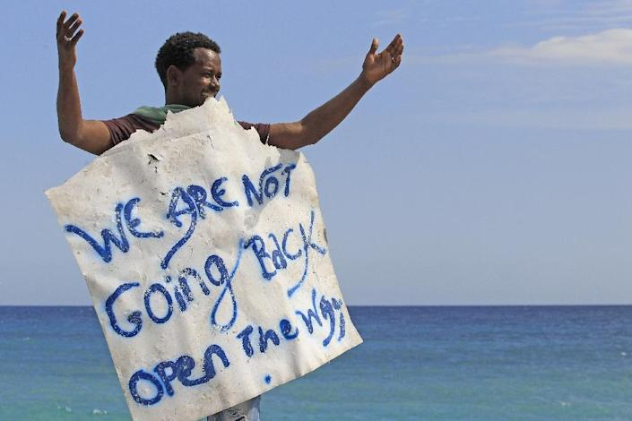 """A migrant holds a sign reading """"we are not going back"""" as he waits near the sea, in the city of Ventimiglia at the French-Italian border, on June 15, 2015 (AFP Photo/Jean-Christophe Magnenet)"""