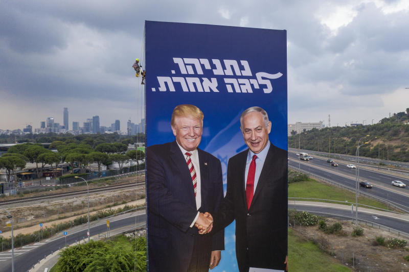 FILE - In this Sept. 8, 2019, file photo, a worker hangs an election campaign billboard of the Likud party showing U.S. President Donald Trump, left, and Israeli Prime Minister Benjamin Netanyahu in Tel Aviv. Netanyahu's recent troubles have some parallels to those of his good friend Trump. Both face an array of corruption allegations, both have lashed out at the media and investigators, and both suffered major setbacks this week at the hands of career government officials. (AP Photo/Oded Balilty, File)