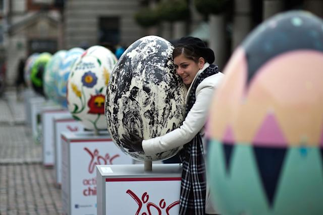 LONDON, ENGLAND - MARCH 22: A visitor poses for a photograph with an egg entitled 'How Mind Came Into The World' by Whitney McVeigh one of the giant fibreglass easter eggs on display in Covent Garden before the Big Egg Hunt on March 22, 2013 in London, England. Each egg is two and a half feet tall and designed by a leading artist. (Photo by Bethany Clarke/Getty Images)