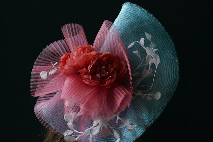 A woman wears a light blue hat with a cloth red rose on it.