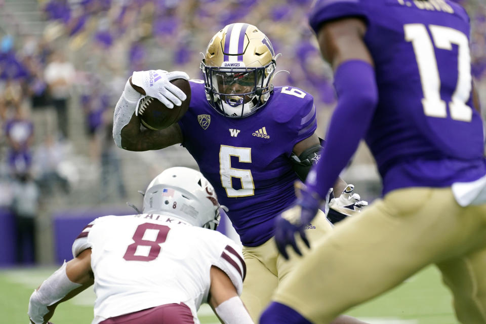 Washington's Richard Newton (6) carries the ball as Montana's Corbin Walker (8) moves in to defend in the first half of an NCAA college football game Saturday, Sept. 4, 2021, in Seattle. (AP Photo/Elaine Thompson)