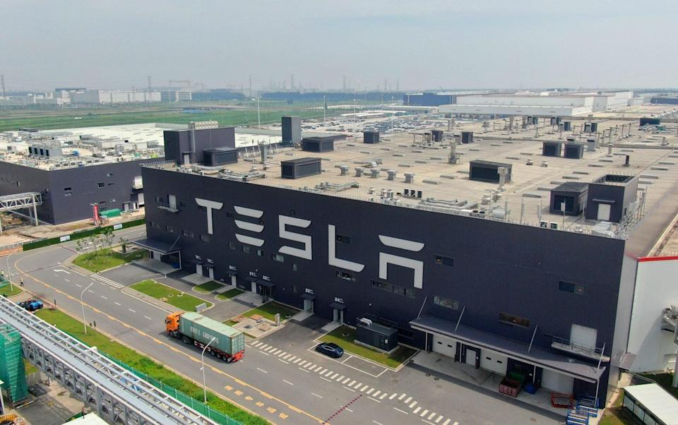 A giant dark grey building marked TESLA, about five or six storeys high and sprawling across a flat plain, looms over a Chinese road where an orange articulated lorry is passing by - Visual China Group/Getty