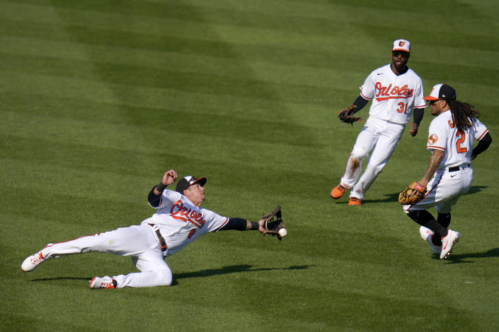 Baltimore Orioles left fielder Ryan Mountcastle, left, attempts a diving catch on a ball hit by Boston Red Sox's Christian Vazquez during the sixth inning of a baseball game, Thursday, April 8, 2021, on Opening Day in Baltimore. Orioles Cedric Mullins (31) and Freddy Galvis (2) look on. (AP Photo/Julio Cortez)