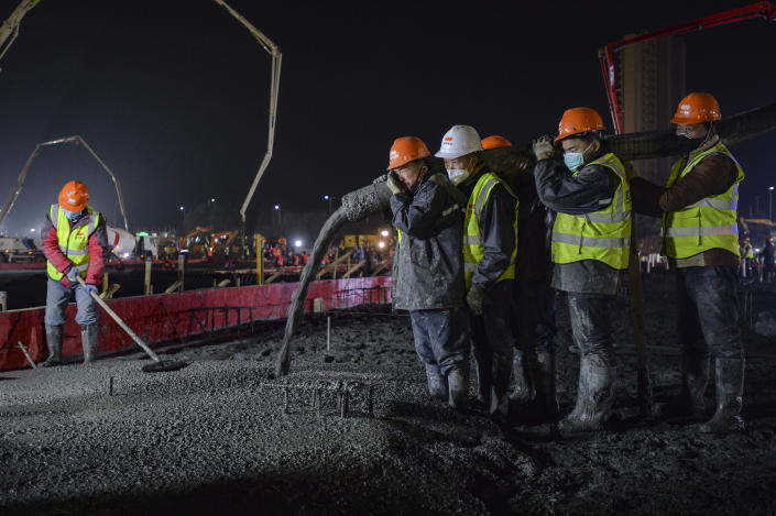 In this Tuesday, Jan. 28, 2020, photo, construction workers labor at the site of the Huoshenshan temporary field hospital being built in Wuhan in central China's Hubei Province. China as of Wednesday has more infections of a new virus than it did in with SARS, though the death toll is still lower. (Chinatopix via AP)
