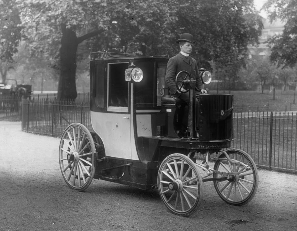 A historical photograph of a man driving a 1896 Bersey Electric cab.