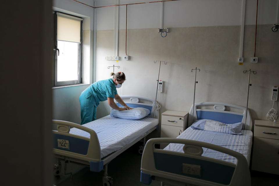 Medical staff check an empty ward, reserved for possible COVID-19 patients, at the Colentina Hospital in Bucharest, Romania, Thursday, Feb. 25, 2021. A year ago, Romania reported its first case of COVID-19, prompting the country's strapped medical system to turn its focus to treating COVID-19 patients. As a result, many patients with other conditions — including HIV but also cancer and other illnesses — have either been denied critical care or stopped going to their regular appointments, fearful of becoming infected.(AP Photo/Vadim Ghirda)