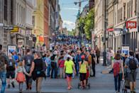 View of Oslo City Hall and street scene with people and traveller / Oslo, Norway