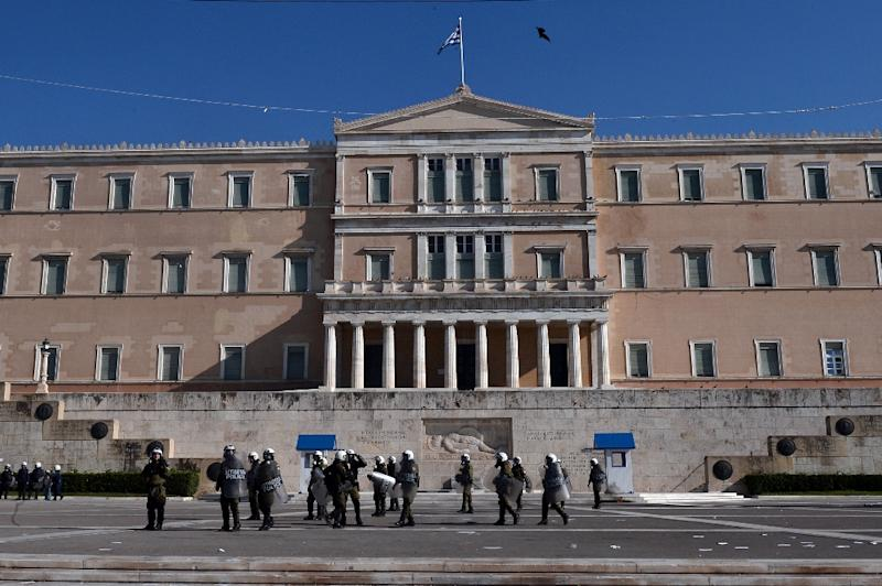 Greek police stand outside Parliament during a massive demonstration against fresh cuts, in Athens on November 12, 2015