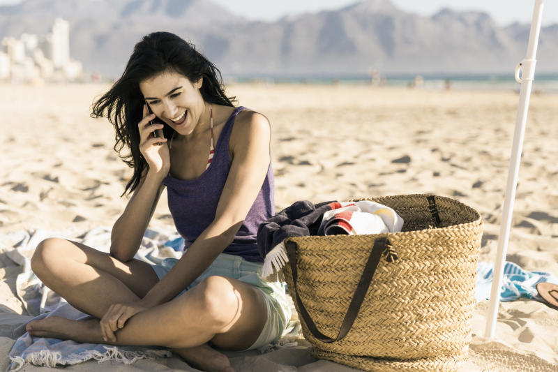 A photo of happy woman talking on phone. Smiling female is wearing casuals. She is at beach.