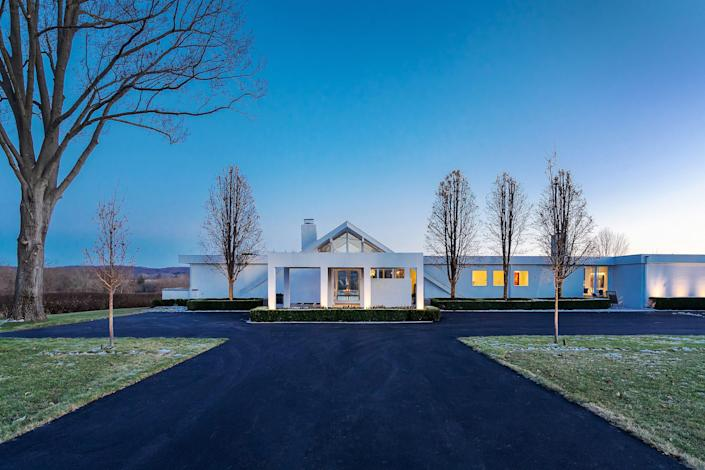 Designed by midcentury architect Jules Gregory, this 1958 brick-and-glass home in Bucks County has been expanded and renovated for contemporary living. The A-frame section of the house features soaring ceilings and glass walls with views of the patio and surrounding farmland. The striking façade is accented with water features, and the rear patio includes a bar, a barbecue, a built-in firepit, and access to the pool.