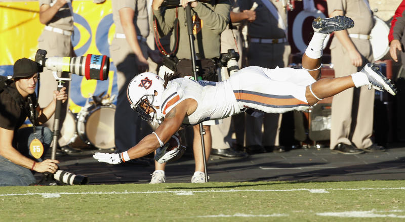 Auburn running back Tre Mason (21) dives for extra yardage after running for 53-yards in the fourth quarter against Texas A&M in an NCAA college football game Saturday, Oct. 19, 2013, in College Station, Texas. Auburn won 45-41. (AP Photo/Bob Levey)