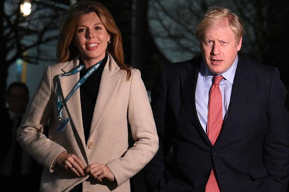 Britain's Prime Minister and Conservative leader Boris Johnson (R) and his partner Carrie Symonds (L) arrive at the count centre in Uxbridge, west London, on December 13, 2019 as votes were counted as part of the UK general election. - Prime Minister Boris Johnson's ruling party appeared on course for a sweeping victory in Thursday's snap election, an exit poll showed, paving the way for Britain to leave the EU next month after years of political deadlock. (Photo by Oli SCARFF / AFP) (Photo by OLI SCARFF/AFP via Getty Images)
