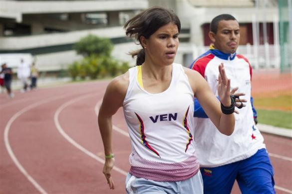 Irene Suarez, 24, a blind runner and her guide Richard Torrealba run during a training session as part of her Paralympic training route in Caracas March 21, 2012.