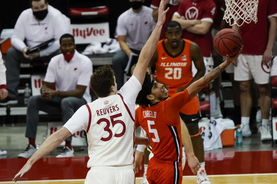 Illinois's Andre Curbelo drives past Wisconsin's Nate Reuvers during the first half of an NCAA college basketball game Saturday, Feb. 27, 2021, in Madison, Wis. (AP Photo/Morry Gash)