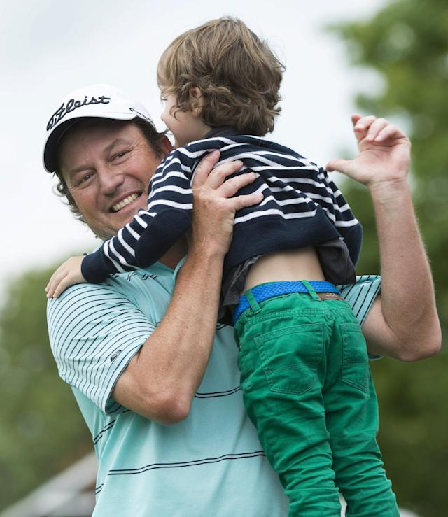 Tim Clark, from South Africa, celebrates with his 3-year-old son, Jack, after winning the Canadian Open golf championship Sunday, July 27, 2014, in Montreal. (AP Photo/The Canadian Press, Paul Chiasson)