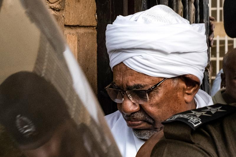Sudan's ousted president Omar al-Bashir is escorted into a vehicle as he returns to prison after appearing before prosecutors over charges of corruption and illegal possession of foreign currency