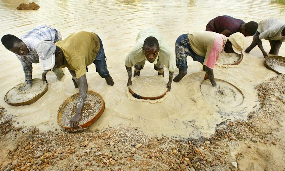 """Miners pan for diamonds near Koidu in northeastern Sierra Leone near the Guinean border, in 2004 file photo. Hollywood's take on """"conflict diamonds"""" has brought attention back in a big way to how gems associated with wealth and glamor have too often meant war and suffering in Africa. The film """"Blood Diamond,"""" which opened Friday, Dec. 8, 2006, in U.S. theaters, is set in late 1990s Sierra Leone, when the West African country was in the throes of a civil war in which untraceable diamonds allegedly funded fighters who hacked off people's hands with machetes and burned entire villages. (AP Photo/Ben Curtis, file)"""