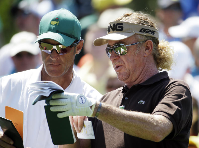 Miguel Angel Jimenez, of Spain, checks his notebook with caddie Clifford Botha before teeing off on the sixth hole during the third round of the Masters golf tournament Saturday, April 12, 2014, in Augusta, Ga. (AP Photo/Darron Cummings)