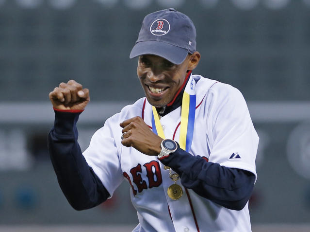 Meb Keflezighi, men's winner of this week's Boston Marathon, reacts after throwing a ceremonial first pitch prior to a baseball game between the Boston Red Sox and New York Yankees at Fenway Park in Boston, Wednesday, April 23, 2014. (AP Photo/Elise Amendola)