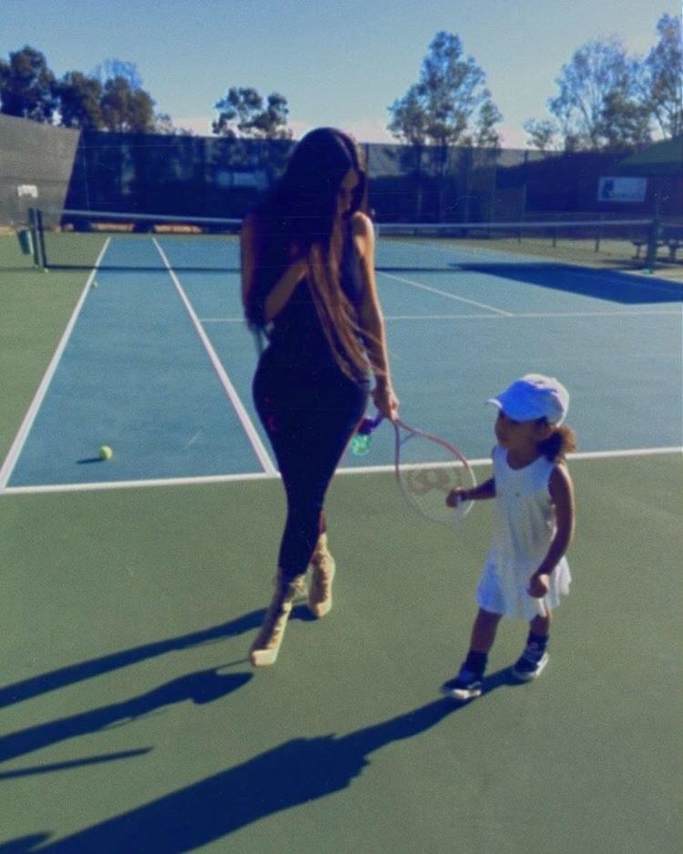 Playing the part of a very chic tennis girl in a white velvet slip dress and matching white hat.