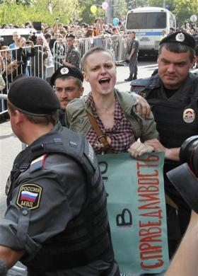 "Police detain a supporter of the female punk band ""Pussy Riot"" for violation of law and order outside a court building in Moscow, August 17, 2012. The banner reads, ""I believe in justice."""