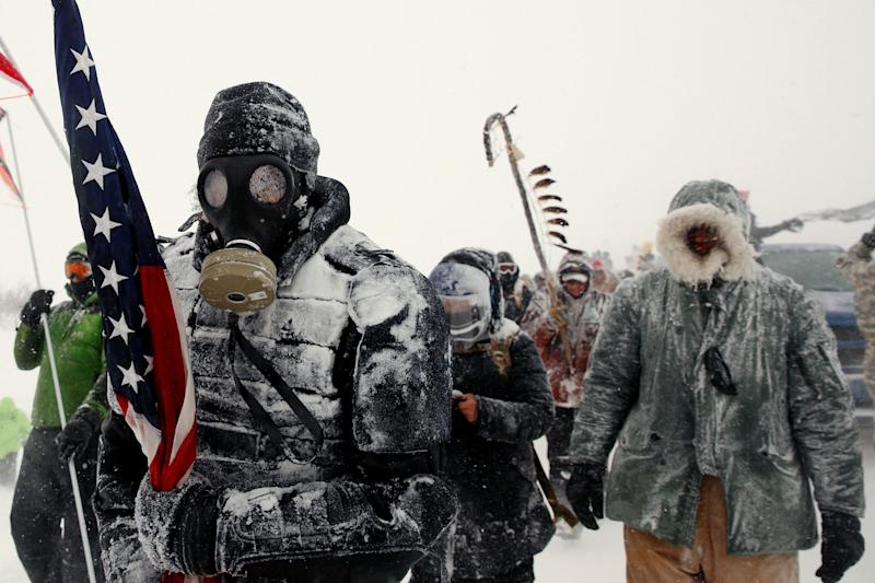 A man takes part in a march with veterans to Backwater Bridge just outside of the Oceti Sakowin Camp during a snow fall as
