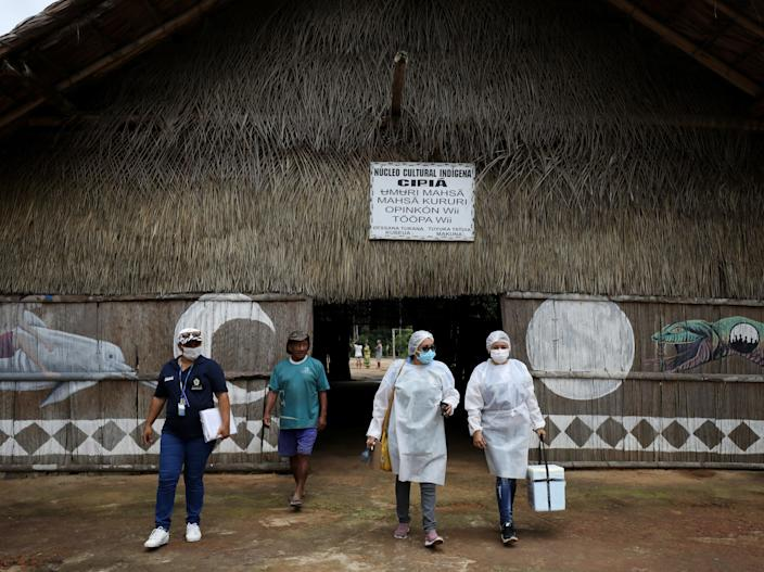 Municipal health workers leave an Indigenous hut after administering the AstraZeneca Covid vaccine in the Sustainable Development Reserve of TupeBruno Kelly/Reuters