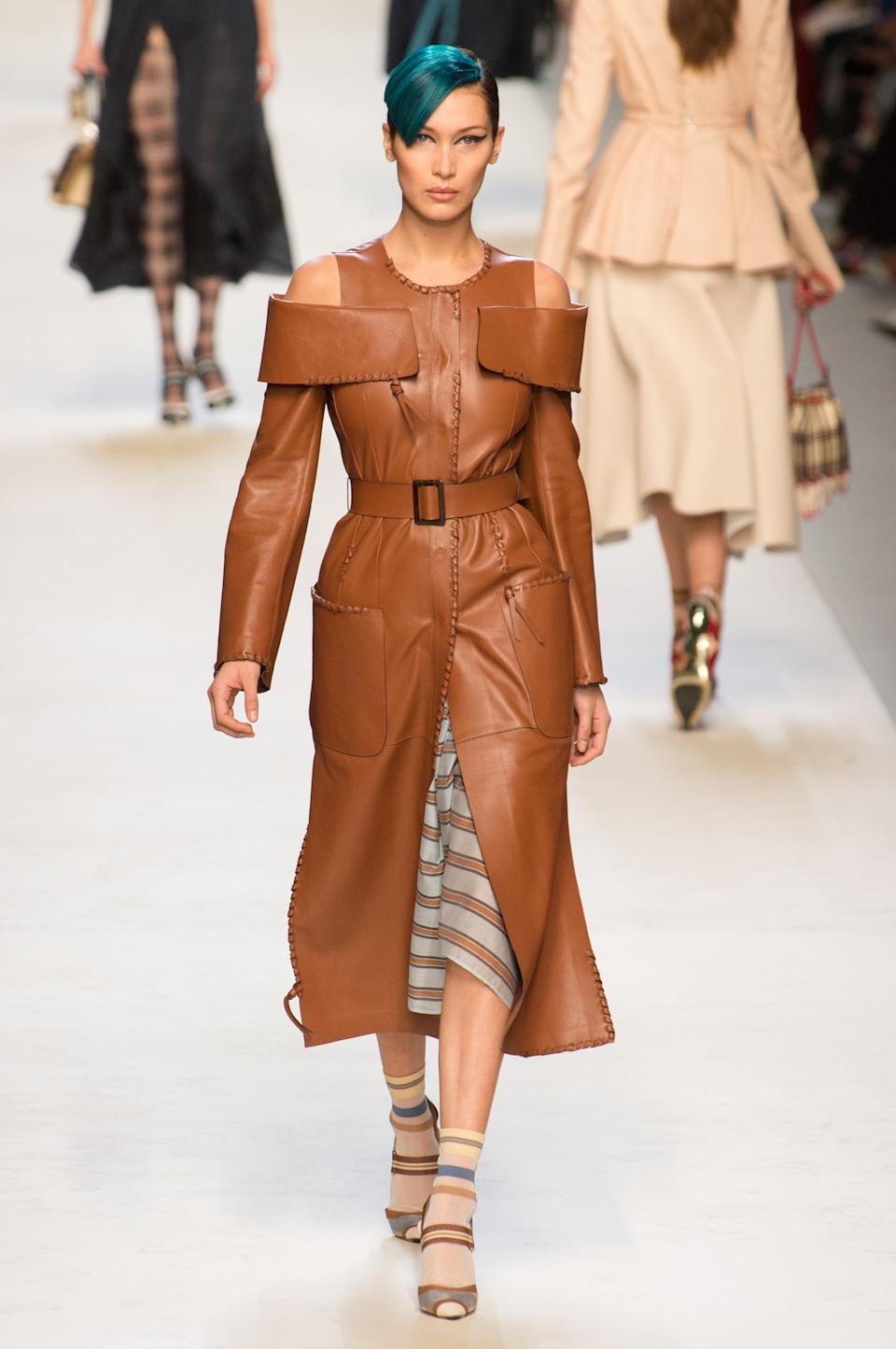 <p><i>Model Bella Hadid wears a brown cold-shoulder belted dress from the SS18 Fendi show. (Photo: ImaxTree) </i></p>