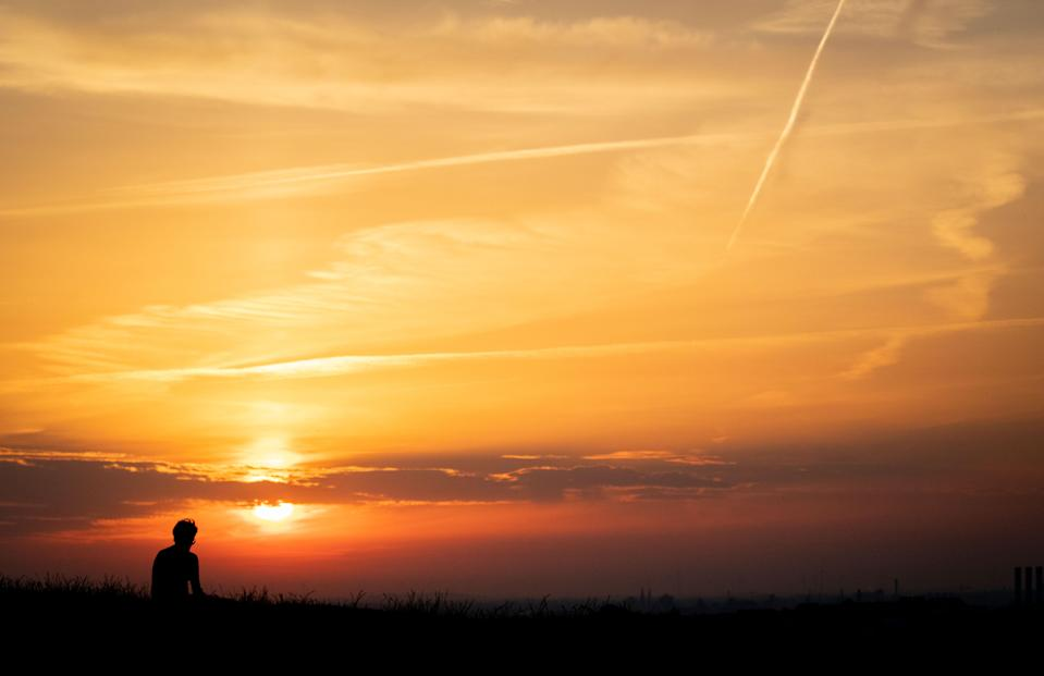 A man sitting at Drachenberg mountain watches the sun rising over Berlin on June 26, 2019). - As Europe sizzled at the start of a heatwave tipped to break records, meteorologists blamed a blast of torrid air from the Sahara for the unusually early summer heatwave, which could send thermometers above 40 degrees Celsius (104 Fahrenheit) in some places in Europe on Thursday and Friday. (Photo by Kay Nietfeld / dpa / AFP) / Germany OUT        (Photo credit should read KAY NIETFELD/AFP/Getty Images)