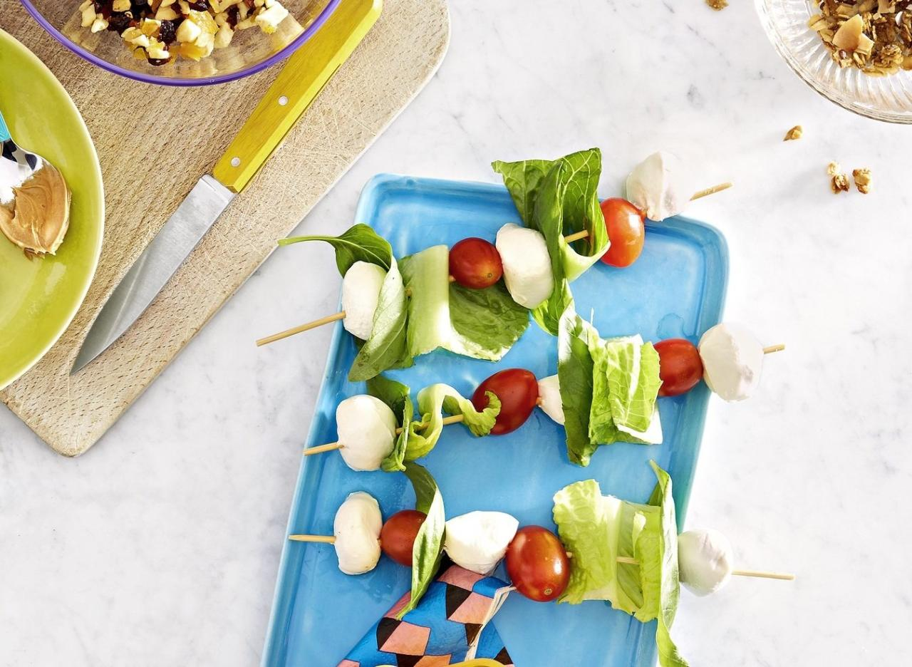 <p>Skewer cherry or grape tomatoes, mini pieces of romaine lettuce, basil, and mini mozzarella balls. Cut off pointy ends. </p>