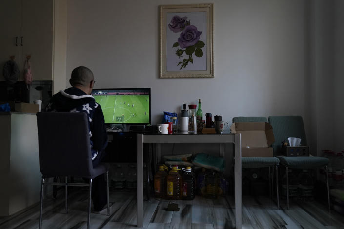 Wuhan resident Zhu Tao plays video game near supplies stocked under a table at home in Wuhan in central China's Hubei province on Wednesday, Oct. 21, 2020. Zhu, a government critic, took precautions against the virus early and felt vindicated when the outbreak exploded and the city went into lockdown. But now that the situation is back to something close to normal in Wuhan, Zhu finds himself at odds with his neighbors and the government. (AP Photo/Ng Han Guan)